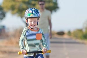 smiling happy little boy at the balance bike and his young father in the background